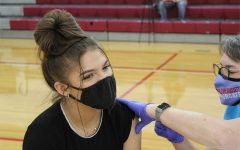 Senior Kenzie Pickens receives her first dose of the Pfizer COVID vaccine on April 9 in the Jack Stephens Gym.